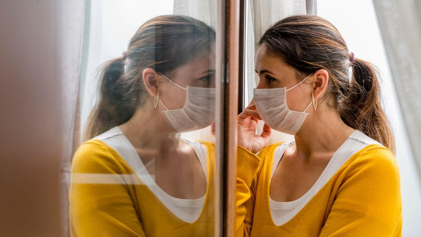 A female coronavirus (Covid-19) or sick patient is forced to self quarantine at her home as she looks through her home window with medical mask to prevent the spread of the virus.
