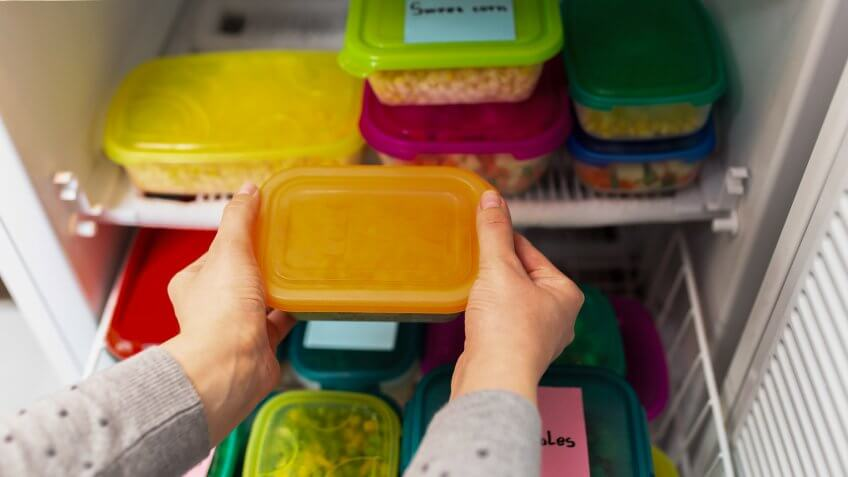 Woman placing container with frozen vegetables in freezer.