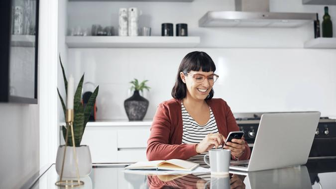 Shot of a young woman using her cellphone while sitting at home with her laptop.