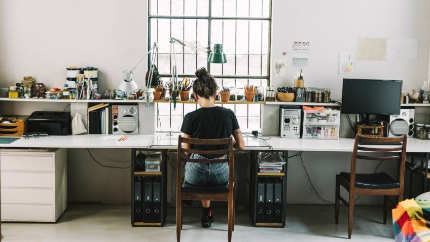 Rear view of artist working at desk.