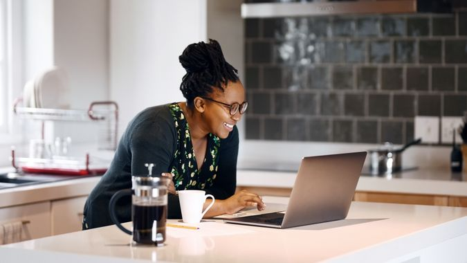 Shot of a smiling young woman using laptop on kitchen counter.