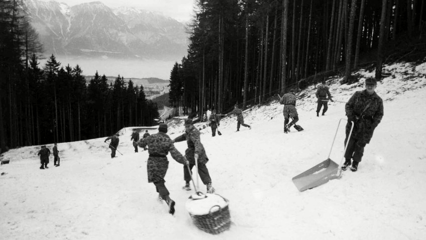Austrian soldiers use baskets to haul snow down to part of the downhill slope that will be used for the Bobsled run in the IX Winter Olympic Games, in Innsbruck, Austria on .