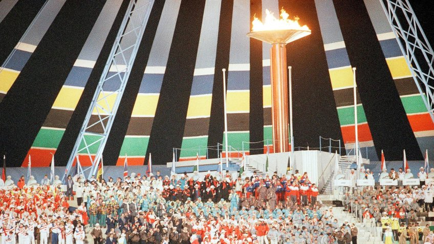 Athletes gather under the Olympic torch during the closing ceremony at the McMahon Stadium in Calgary at night on .