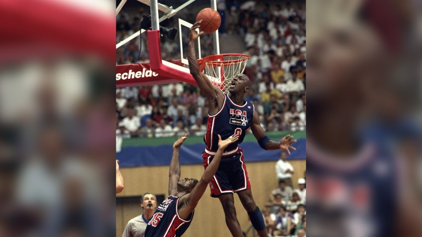 USA's Michael Jordan sails high above teammate Magic Johnson knocking away a shot during the first half of their preliminary round basketball game with Croatia at the Summer Olympics in Barcelona.
