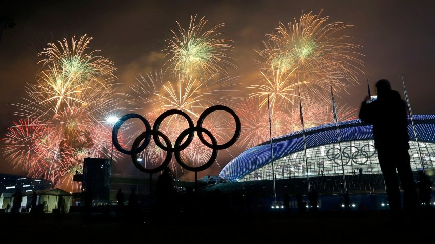A man takes a photograph of fireworks during the closing ceremony of the 2014 Winter Olympics, in Sochi, Russia.