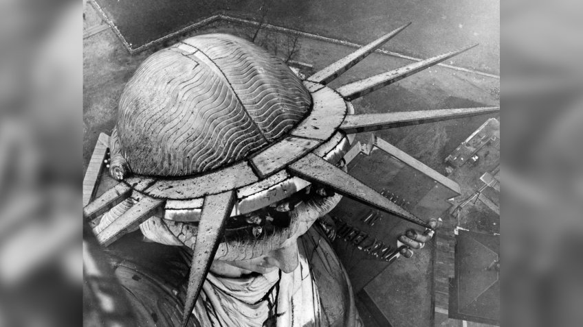 A group of people leaning out of the head of the Statue of Liberty in New York, seen from the torch above.
