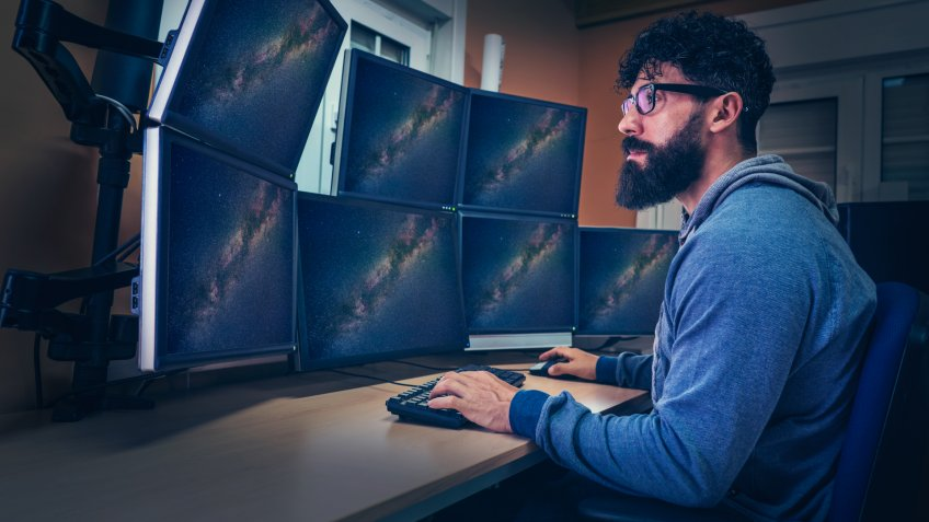 Astronomer in control panel room multi screen sitting profile with beard.