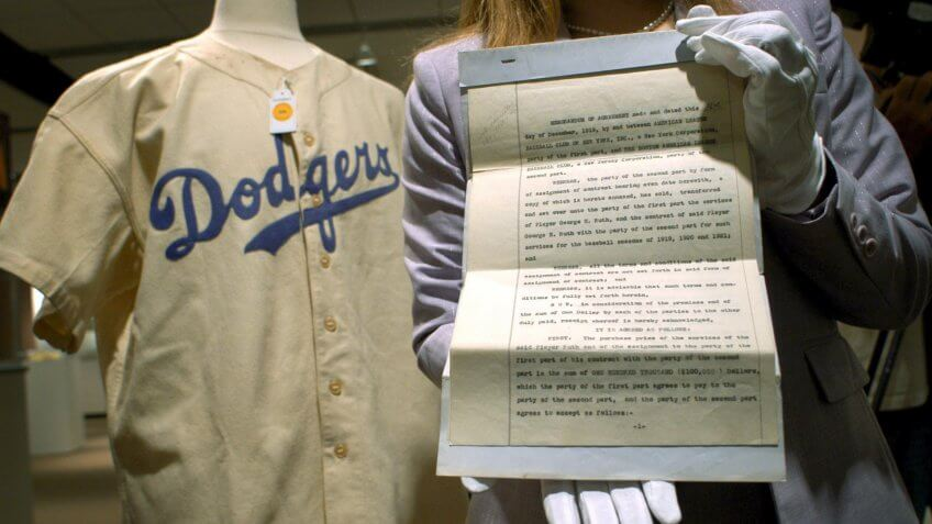 Mandatory Credit: Photo by Justin Lane/EPA/Shutterstock (7832497a)The Hands of a Sotheby's Employee Hold Up the Original 1919 Contract (r) That Traded Baseball Player Babe Ruth From the Boston Red Sox to the New York Yankees Next to Ruth's 1938 Brooklyn Dodgers Uniform (l) During a Preview of a Sports Memorabilia Auction to Take Place 10 June 2005 at Sotheby's Friday 3 June 2005 in New York the Contract Seen Here is Expected to Sell For Over $500 000 (usd) the Uniform For Over $150 000 (usd) and the Money Will Go to a Hunger Relief CharityUsa New York Sports Memorabilia Auction - Jun 2005.