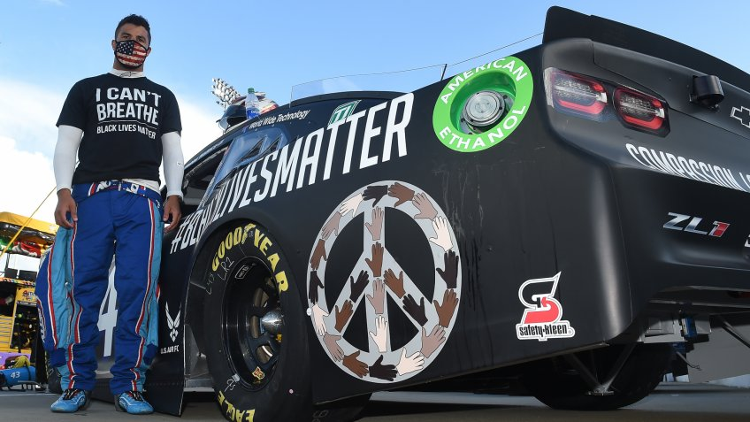 "MARTINSVILLE, VIRGINIA - JUNE 10: Bubba Wallace, driver of the #43 Richard Petty Motorsports Chevrolet, wears a ""I Can't Breathe - Black Lives Matter"" t-shirt under his fire suit in solidarity with protesters around the world taking to the streets after the death of George Floyd on May 25 , stands next to his car painted with ""#Black Lives Matter"" prior to the NASCAR Cup Series Blue-Emu Maximum Pain Relief 500 at Martinsville Speedway on June 10, 2020 in Martinsville, Virginia."