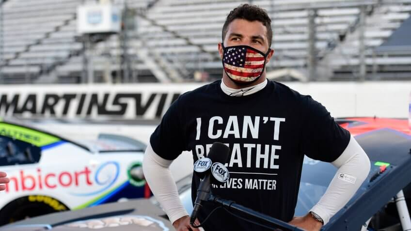 "MARTINSVILLE, VIRGINIA - JUNE 10: Bubba Wallace, driver of the #43 Richard Petty Motorsports Chevrolet, wears a ""I Can't Breathee - Black Lives Matter"" t-shirt under his fire suit in solidarity with protesters around the world taking to the streets after the death of George Floyd on May 25, speaks to the media prior to the NASCAR Cup Series Blue-Emu Maximum Pain Relief 500 at Martinsville Speedway on June 10, 2020 in Martinsville, Virginia."