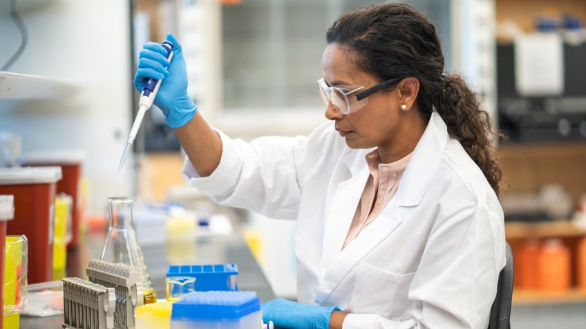 An ethnic female biochemist is working in a laboratory.