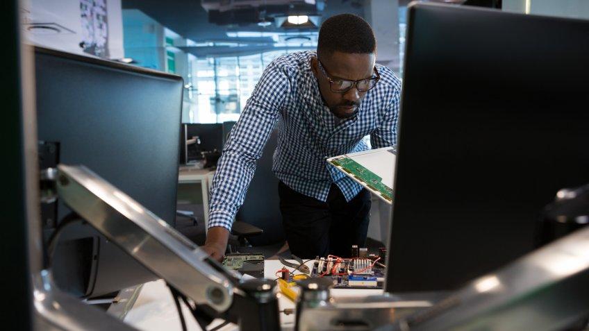 Computer engineer repairing motherboard at desk in office.