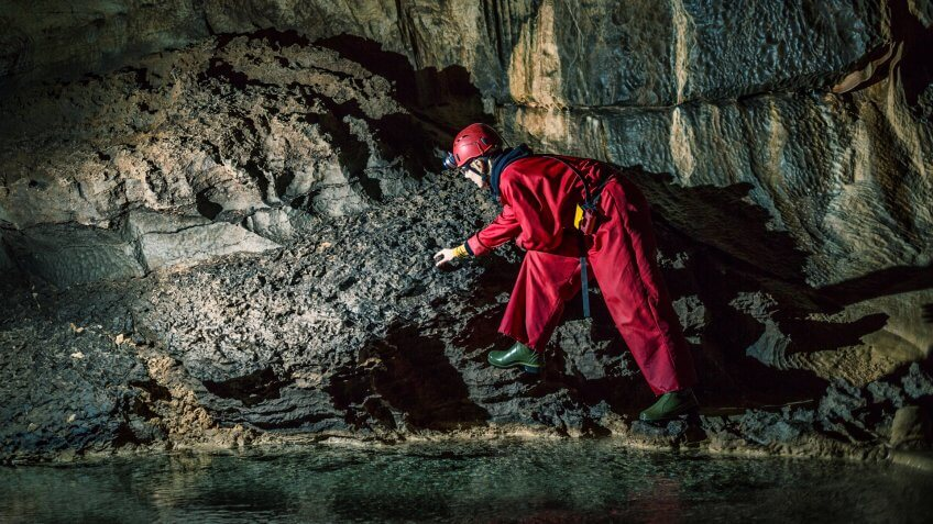 Geologist exploring caves deep underground.