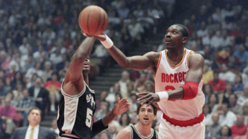 Houston Rockets center Hakeem Olajuwon (34) shoots around San Antonio Spurs center David Robinson as Spurs guard Vinny Del Negro (15) looks on during the first quarter of Game 3 of the Western Conference finals, in HoustonSpurs vs Rockets, Houston, USA.
