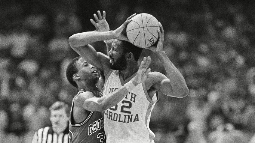 North Carolina forward James Worthy holds the ball away from Georgetown's Eric Smith during the NCAA championship game in New Orleans, .
