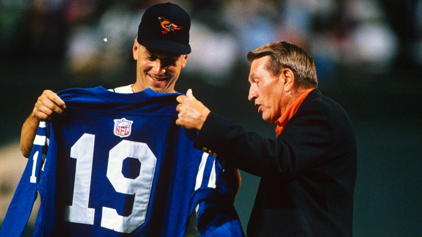 BALTIMORE, MD - SEPTEMBER 8: Former Baltimore Colt and football great Johnny Unitas presents one of his #19 jerseys to Cal Ripken Jr #8 of the Baltimore Orioles during an Major League baseball game September 8, 1995 at Oriole Park at Camden Yards Baltimore, Maryland.