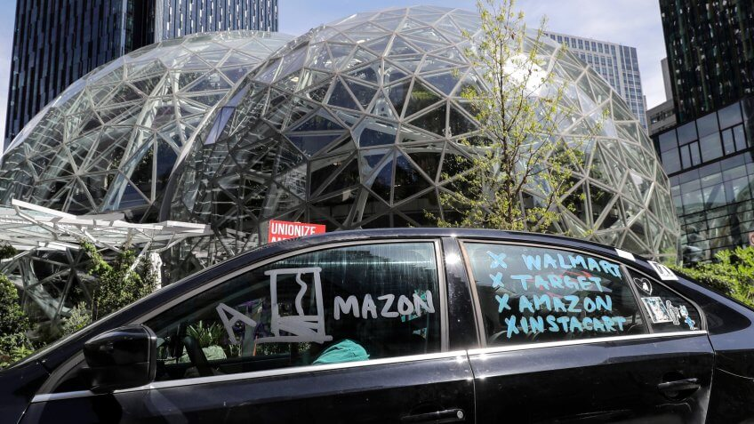 Mandatory Credit: Photo by Ted S Warren/AP/Shutterstock (10631590i)Protester drives a car with writing that calls for a general strike by workers from Walmart, Target, Amazon, and Instacart during a car-based protest, at the Amazon Spheres in downtown Seattle.