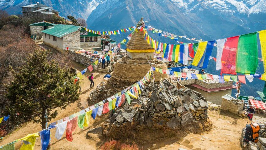 Namche Bazaar, Nepal - November 2, 2014: Hikers trekking past a traditional stupa shrine festooned with colourful Buddhist prayer flags fluttering in the breeze above a collection of Sherpa teahouses and lodges deep in the Himalayan mountains of the Everest National Park, a UNESCO World Heritage Site, Nepal.