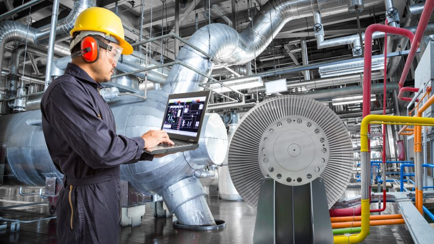 Engineer using laptop computer for maintenance in thermal power plant industrail.