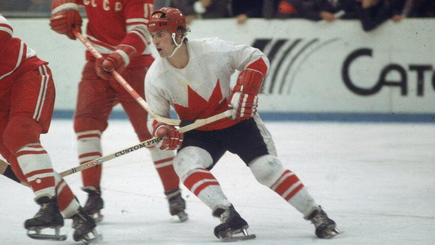 Canadian professional hockey player Paul Henderson (right), left wing for Team Canada, skates by two players from the Soviet team during a game from the Summit Series, 1972.