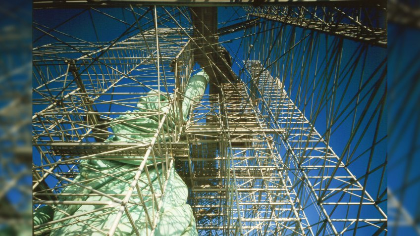Statue of Liberty during restoration, looking straight up torch arm showing scaffolding and draped robe, Liberty Island, New York City, c.