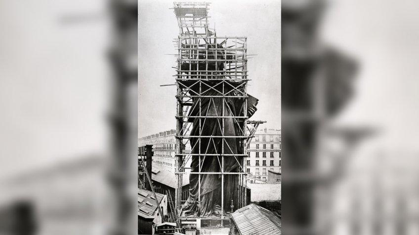 """Statue of Liberty in scaffolding at its manufacturing site in Paris before it was shipped to New York city, 1883, plate 12 from """"Album des Travaux de Construction de la Statue Colossale de la Liberté destinée au Port de New-York""""Art - various."""