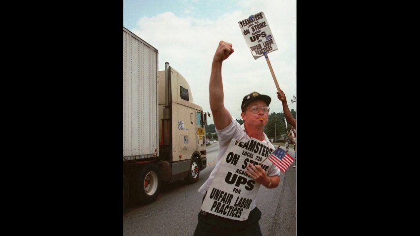 Mandatory Credit: Photo by John Bazemore/AP/Shutterstock (6530237a)MILLER Striking United Parcel Service driver David Miller reacts as a passing truck driver blows his vehicle's horn before a rally in front of the UPS distribution center in Tucker, Ga.