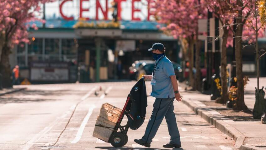 Seattle, USA – April 13, 2020: Late in the day a mailman wearing a mask crossing the street by Pike Place Market at the height of the Coronavirus city wide shutdown.
