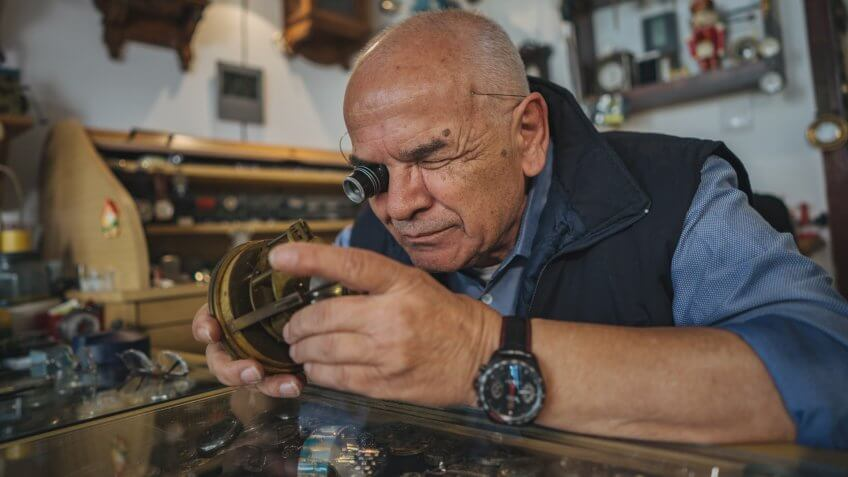 Senior watchmaker repairing old clock in his workshop.