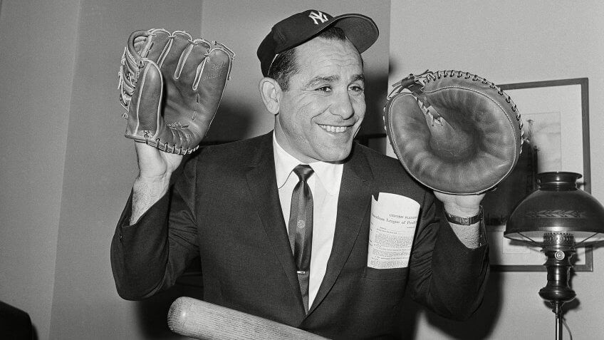 Yankee veteran Yogi Berra wears catcher's mitt and fielder's glove, as he sits in the downtown office of the New York Yankees in New York, after signing his contract for 1961.