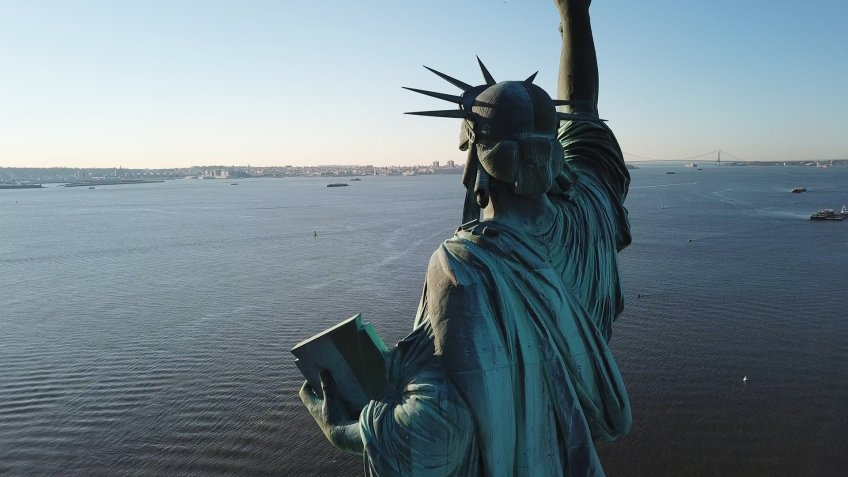 NEW YORK - MARCH 11, 2018: aerial view of Statue of Liberty from the rear overlooking blue water in NYC. The statue stands 305 feet and 1 inch from the ground.