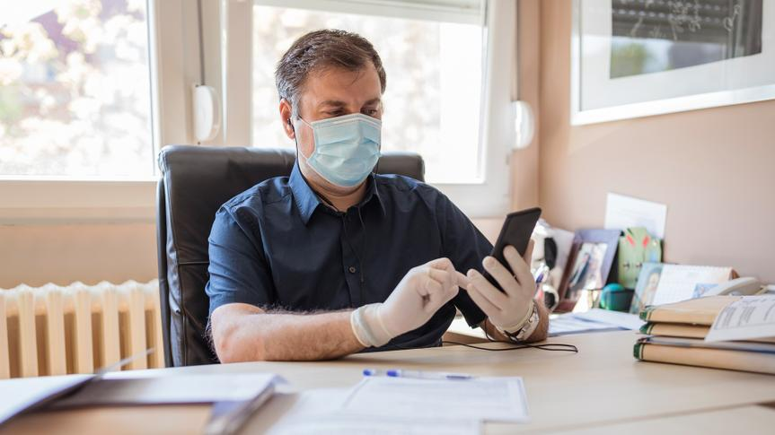 boss answering phone call with mask and gloves in office with protective mask and gloves holding mobile phone.
