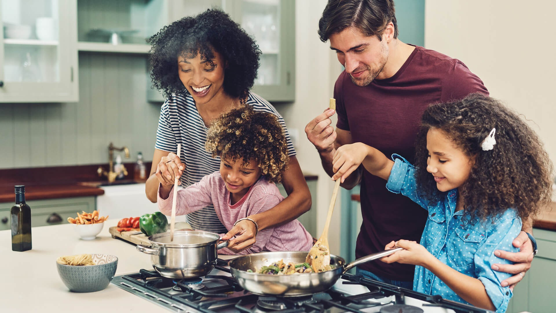 Shot of a family of four cooking together in their kitchen at home.