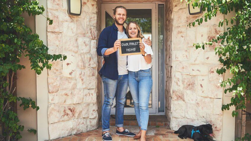 """Portrait of a young couple holding a chalkboard with """"our first home"""" written on it."""