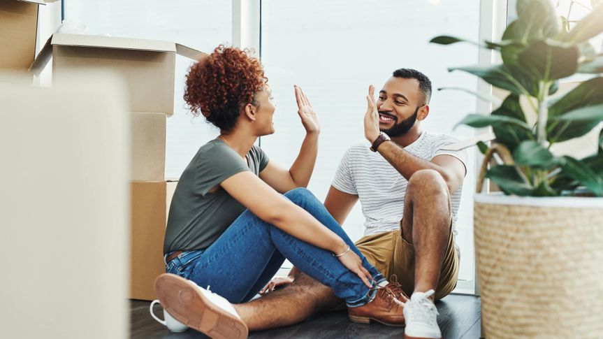 Shot of a young couple giving each other a high five while moving house.