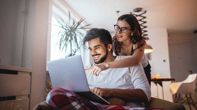 Shot of a happy young couple embracing while using laptop at home.