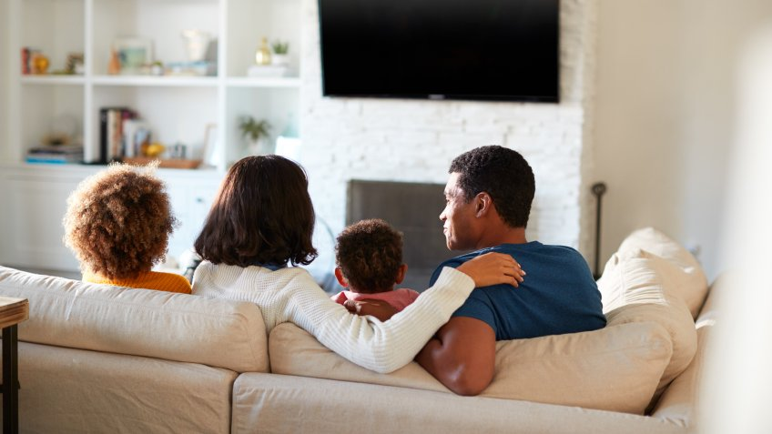 Back view of young family sitting on the sofa and watching TV together in their living room, close up.