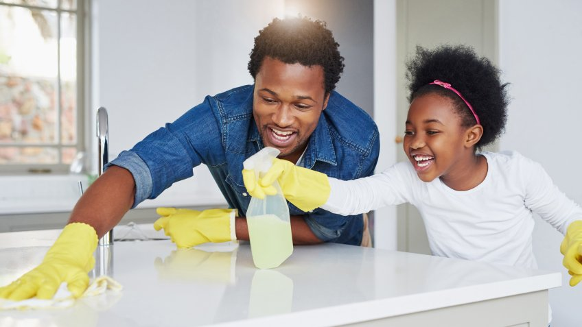Shot of a little girl and her father enjoying their chores at home.