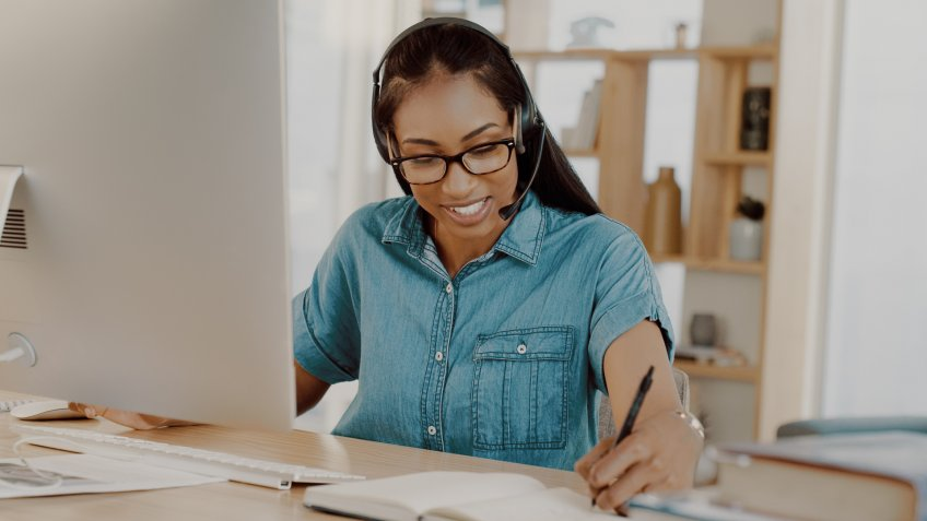 Shot of an attractive young businesswoman wearing headsets and working on a computer at home.