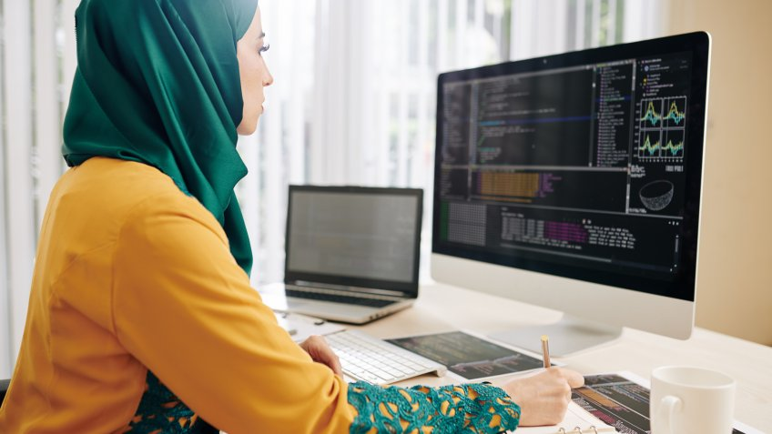 Young woman in hijab checking code implementation and taking notes in planner.