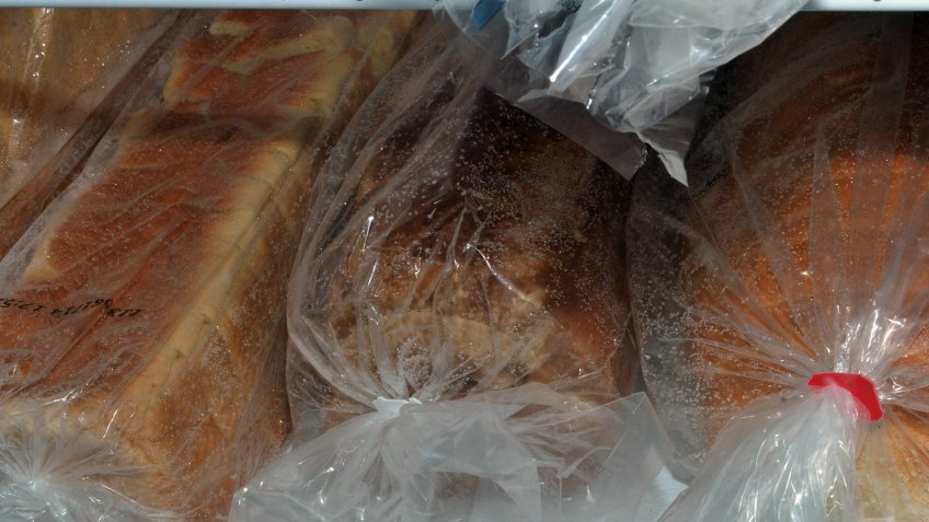 Four bread loaves in a freezer.