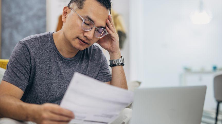 Sad man looking at his monthly bills at home.
