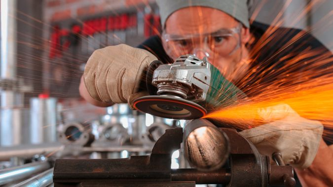 man work in home workshop garage with angle grinder, goggles and construction gloves, sanding metal makes sparks closeup, diy and craft concept.