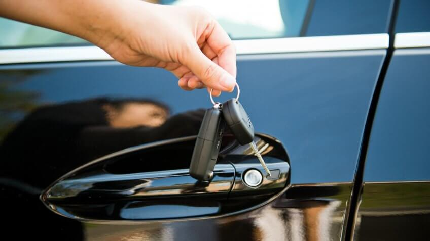 Image of human hand holding a car key  a remote control.