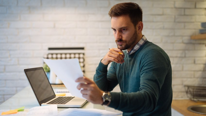Male businessman working at home on a computer.