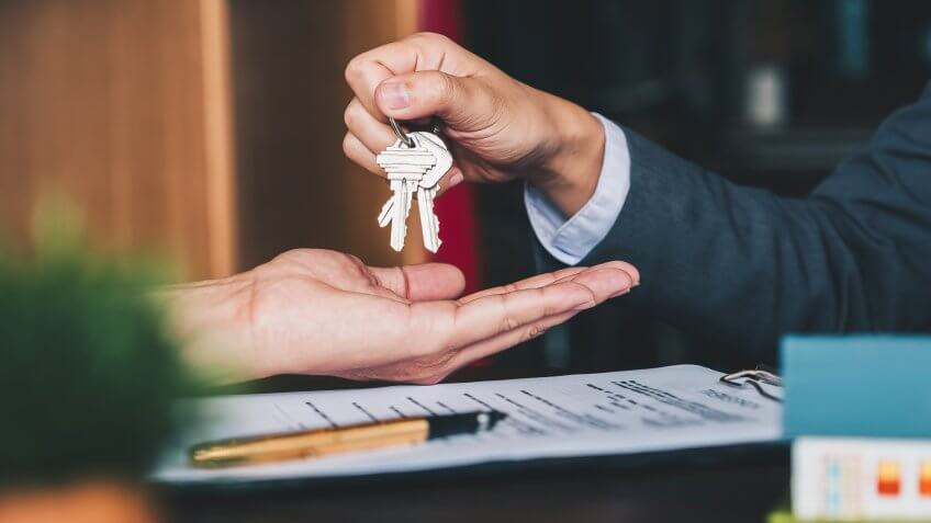 estate agent giving house keys to woman and sign agreement in office.