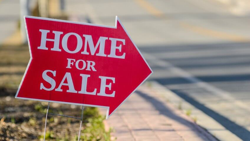 A home for sale sign pointing directing people to a house for sale.