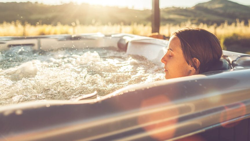 Woman in whirlpool hot tub at sunset.