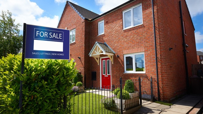 Residential home with For Sale sign out the front.