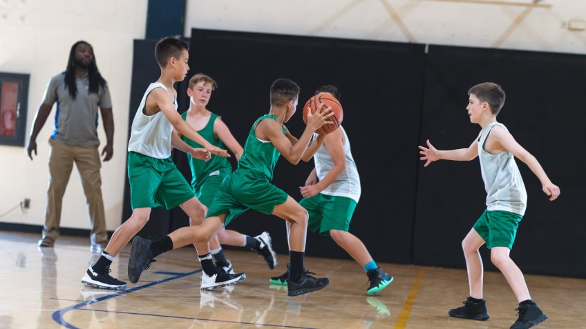 A young African American boy dribbles around three defenders and tries to score.